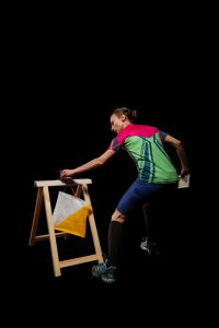 Woman punching at control point, taking part in orienteering competitions. Isolated on black. File contains clipping path